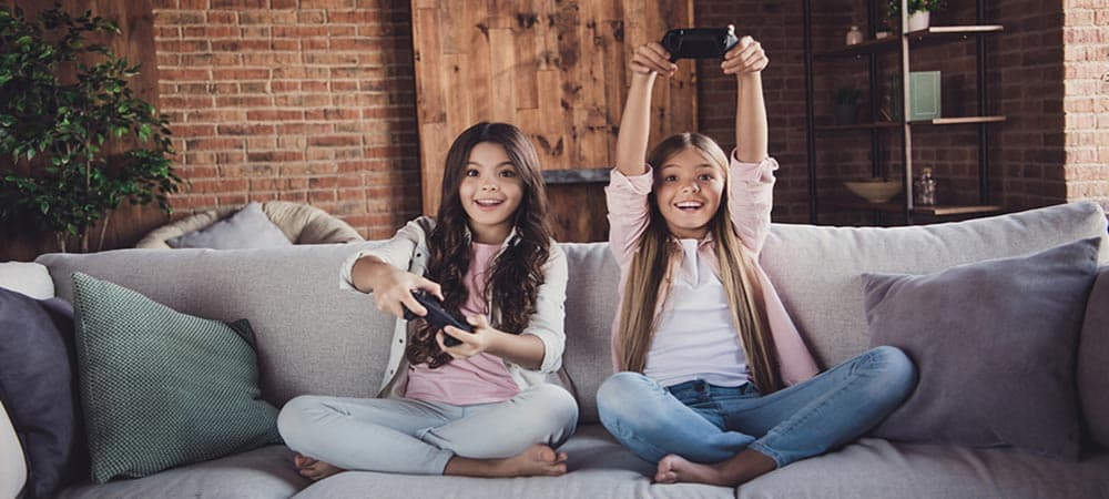 A two kids sitting on sofa and hold video game remotes