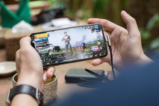 A person holding a phone and playing game