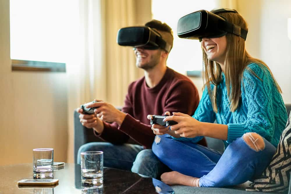 A two people sitting on sofa and playing vr game